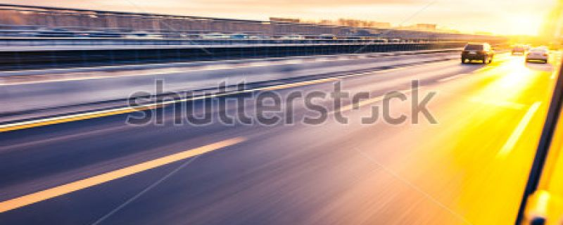 stock-photo-car-driving-on-freeway-at-sunset-motion-blur-205799656